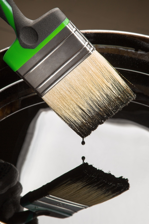 photorealism: drop drips from a brush on a can with the construction mastic Stock Photo