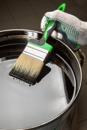 photorealism: hand holding a brush on a can with black mastic construction