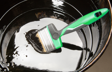 Paint brush in a jar of thick black mastic