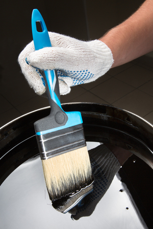 photorealism: Builders gloved hand holding a brush over a can of mastic