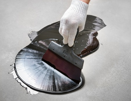 photorealism: Work with a spatula on the bitumen on the surface Stock Photo