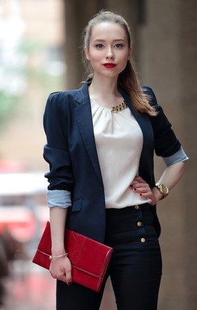 temperament: young girl in a business suit and a red handbag on the street