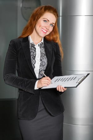 rigor: woman with documents and pen smiling and looking at the frame Stock Photo