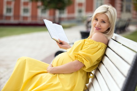 pregnant blonde: Pregnant blonde girl in a yellow dress on a park bench reading a book