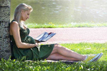 pregnant blonde: Pregnant blonde girl sits under a tree in a park and reading a book