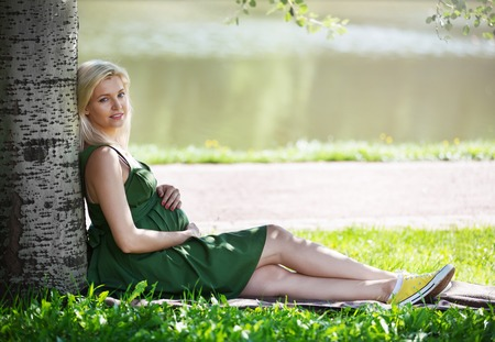 pregnant blonde: Pregnant blonde girl in a green dress sitting under a tree in the park Stock Photo
