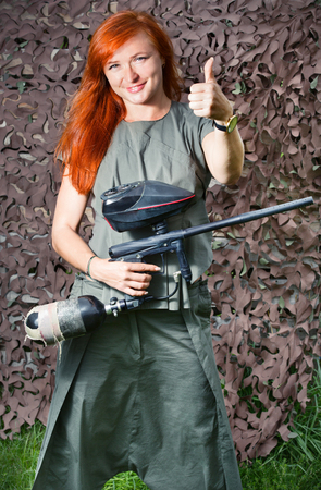 A girl holds a paintball gun and motioned showing thumbs up