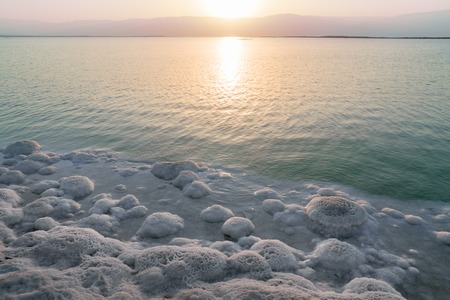 nascent: Landscape with nascent away sunrise and drifting man on the shore of the Dead Sea in Israel Stock Photo