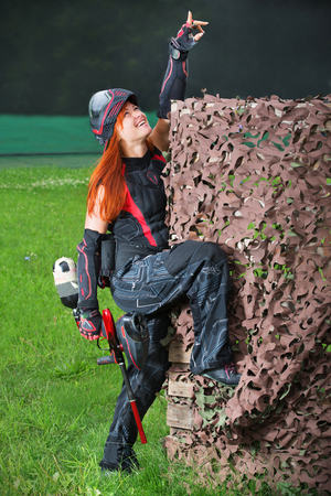 Girls playing paintball shows hand up