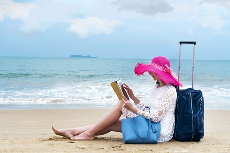 The girl tourist sits on the beach hold her ipad with luggage bag