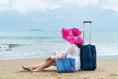 The girl tourist sits on the beach with luggage bag and looks into the distance Stock Photo