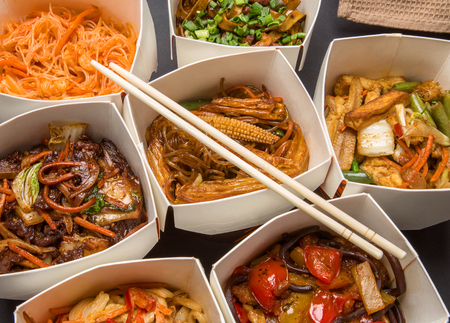 Chinese food in different cardboard boxes and wooden sticks Stock Photo