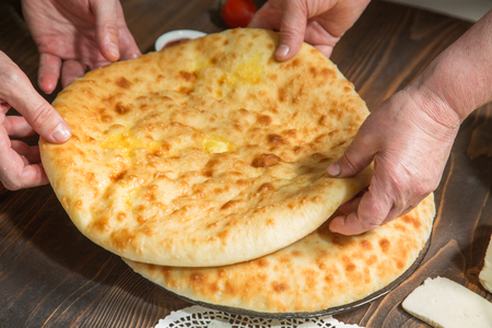 adjective: Bakers hands folded Ossetian pies on the table