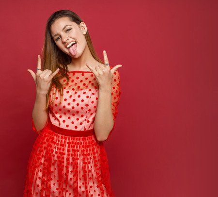 The girl shows gestures and tongue on a colored background