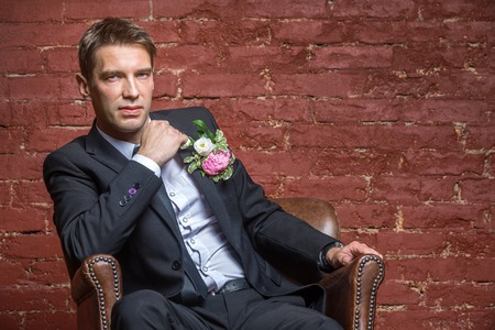 barbershop: serious bridegroom looking and sits in a leather chair against a brick wall