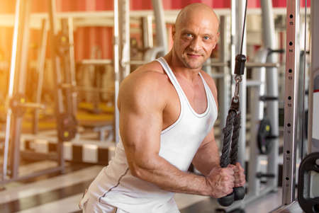 man is engaged in a sports trainer in the gym Stock Photo