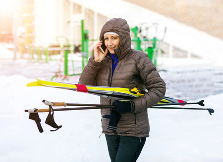 woman holding skis, goes on winter Park and talking on mobile phone