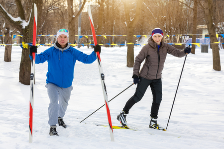 sports man and sports woman with skis in winter Park Stock Photo