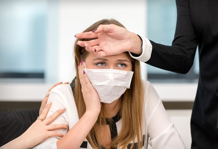 Office life. The girl with a cold working in the office with medical mask Stock Photo