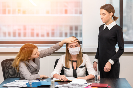 The girl fell ill in the office and colleagues to check her temperature. Office life Stock Photo