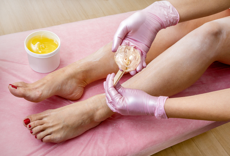 sugaring feet in a beauty salon using cosmetics from a jar