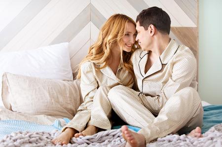 pareja amorosa se despierta por la mañana en su cama en un interior luminoso. Feliz pareja sonriente tumbado en la cama en su casa. Vida familiar