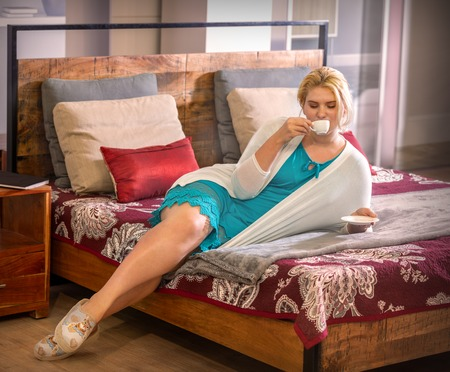 girl resting on the bed in the bedroom with a up of coffee