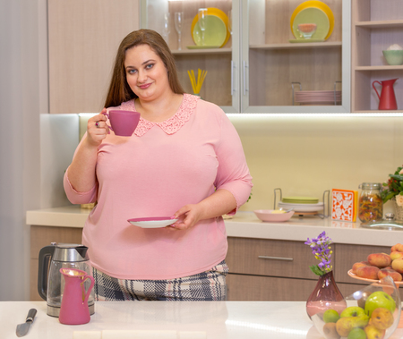 full girl with cup in hand in the kitchen. domestic life Standard-Bild