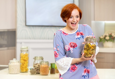 redheaded girl emotionally holding a jar of pasta in her kitchen