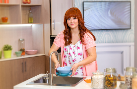 housewife is going to wash dishes and smiles. domestic life Banque d'images