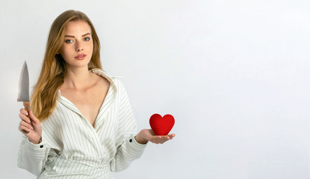 blonde girl holding a knife and heart. love the concept, Valentine, relationship