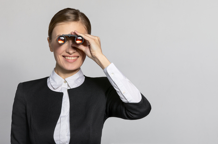 Businesswoman looking through binoculars to the side and smiles.. The concept of the business and finding success. Model in a suit on a light gray background of the Studio