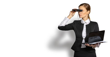businesswoman with a laptop in his hand looking through binoculars in the hope of prospects and success. The concept of business and finance. Isolated background