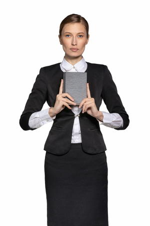 a girl in a strict dress with a book in her hands thinks about what she has read. The concept of religion and a serious girl in a strict monotonous office suit