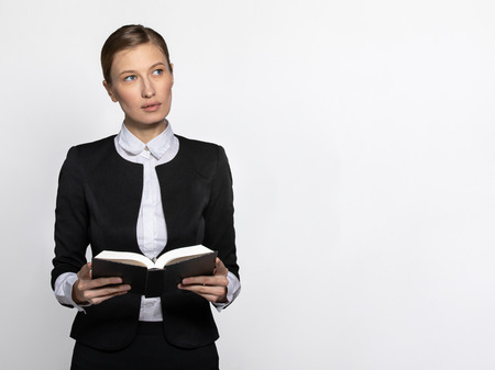 a girl in a strict dress with a book in her hands thinks about what she has read. The concept of religion and a serious girl in a strict monotonous office suit. space for text and copy paste