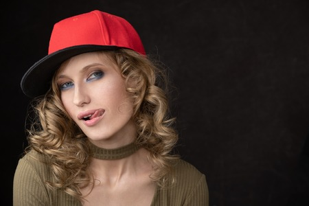 Portrait of naughty girl in red cap and with tongue. Space for text and copy-paste. Dark Studio background and a vivid portrait of the model Imagens