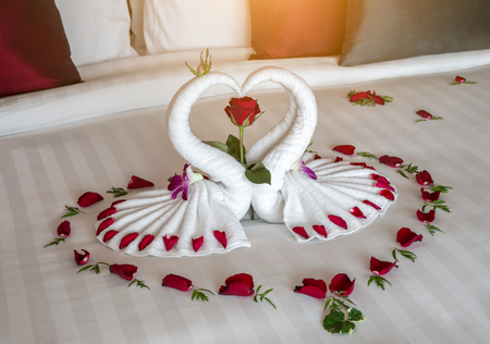figure of swans made out of towels on the bed. bed decoration with flowers and rose petals, romantic interior Banco de Imagens - 114467156
