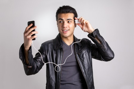 a young man in a black leather jacket charges your cell phone from the head. the concept of the new technology Фото со стока