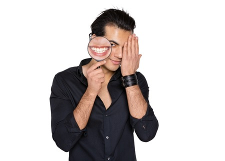the man smiles and shyly closes his eyes with his hand in his hands a magnifying glass with a picture of a wide smile and healthy teeth. Stock fotó