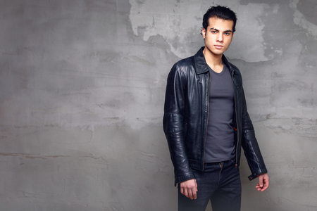 portrait of a man at the cement wall. A young man in a black leather jacket. Free space for text and copy paste.