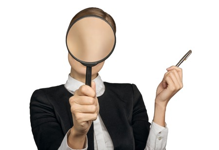 The girl in the office covered her face with a magnifying glass and we do not see her face. Isolated background. The concept of employment and work.