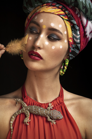 The model poses in the image of an Oriental Princess in a photo Studio on a dark background. model in a bright outfit and with a lizard on his shoulder. bird feather near her face