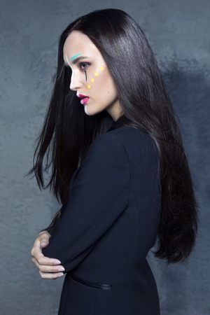 Model with dark hair looks strictly and sadly in the frame. against the Studio wall. girl in profile