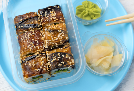 portion of rolls with eel with wasabi and ginger on a plastic blue plate on a white table