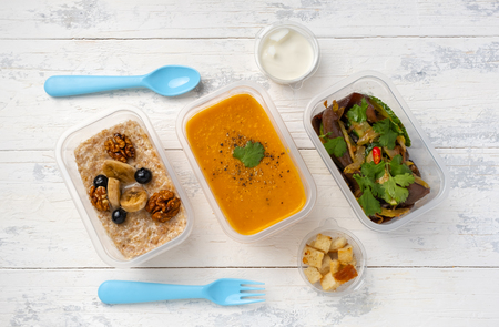 three portions of food consisting of pumpkin soup, eggplant salad and porridge with bananas and nuts on a white wooden table. on the table next to the blue plastic spoon and fork. next to croutons and sour cream.