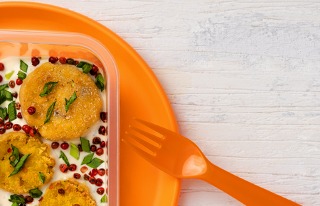 vegetarian cutlets with berries and green onions in sauce. food in a plastic container on a plastic orange plate lying on a white wooden table. free space for text and copy paste