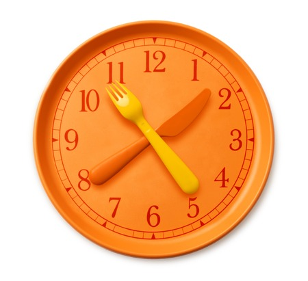 isolated watch on the orange plate, where instead of arrows yellow orange fork and knife. plastic utensils and clock on the table. concept of diet and health