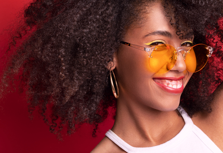 smiling model with dark curly hair in orange glasses on a red background of the Studio. smiles and looks playfully. There is a place for copy paste
