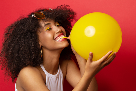 Mulatto model with a lush hairstyle of curly black hair inflates a yellow balloon on a red Studio background Banco de Imagens
