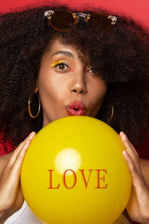 a dark-skinned model with a yellow balloon on which love is written Banco de Imagens